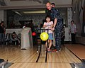 US Navy 100729-N-2653B-079 Aviation Boatswain's Mate (Handling) 1st Class Nathan Hart assists a Japanese child with bowling at the Wamlsey Bowling Center.jpg