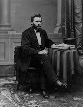 Fotografia portreto da Grant sidanta ĉe tablo kun malferma libro kaj cilindro sur ĝi