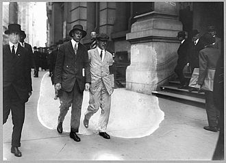 Upton Sinclair - Upton Sinclair wearing a white suit and black armband, picketing the Rockefeller Building in New York City