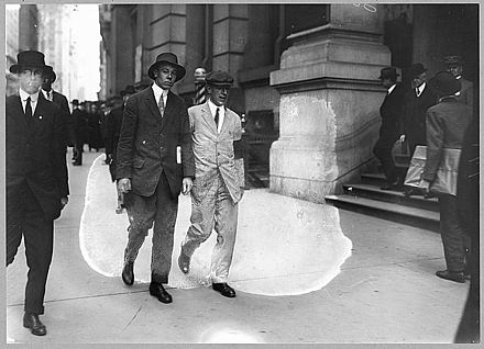Upton Sinclair wearing a white suit and black armband, picketing the Rockefeller Building in New York City Upton sinclair white suit black armband picketing rockefeller bldg.jpg
