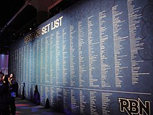 "A long list of songs and artists against a blue background on a wall. About three quarters of the way down the wall is a white line; the songs above the line are labeled ""Rock Band Setlist"" while the songs below it are labeled ""RBN""."