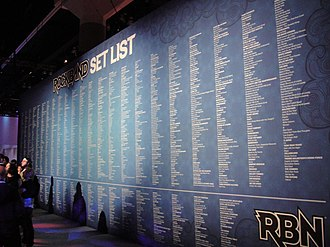 Rock Band 3 - A list of Rock Band songs displayed on the wall at E3 2010. The upper part of the wall lists songs released by Harmonix, either on a game disc or as downloadable content. The lower part shows Rock Band Network songs.