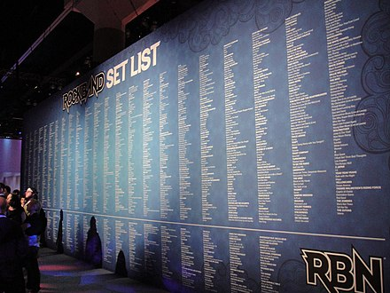 A wall display of the available songs to Rock Band 3 players as of the 2010 Electronic Entertainment Expo, with all in-game and official downloadable content on the upper portion, and the Rock Band Network songs on the bottom portion Wall of Rock Band songs (E3 2010).jpg