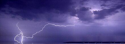 Fulmini durante un temporale notturno colpiscono terra. L'energia irraggiata come luce converte il gas dell'atmosfera in plasma e viceversa