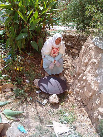 Baking - A Palestinian woman baking markook bread on tava or Saj oven in Artas, Bethlehem