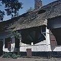 Zicht op gedeelte van de langgevelboerderij uit de Limburgse Kempen met de botermolen of hondekarn, molen werd later toegevoegd, staat in het Openluchtmuseum te Bokrijk, Genk - Bokrijk - 20370279 - RCE.jpg