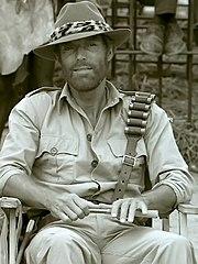 Richard Chamberlain sitting on a film set