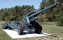 a shield-less mid-green artillery piece sitting on a concrete slab