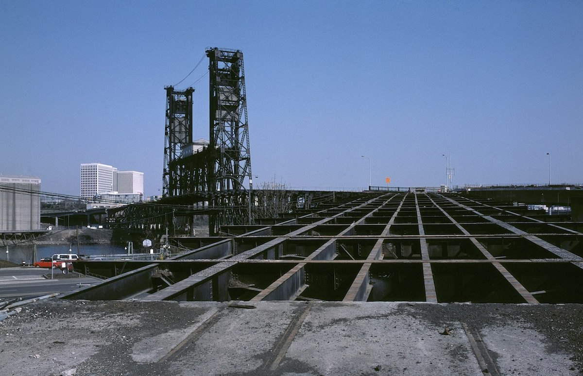 Photograph showing a lattice of steel girders on the Glisan Street ramp of the 1912 Steel Bridge, in Portland as redecking work is under way