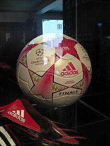 A football in a perspex cabinet. The ball is predominantly white, patterned with stars in red with gold detailing. In the foreground is a black football boot with red and white trim.