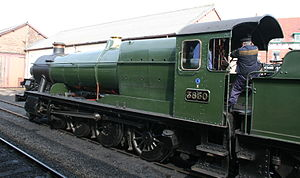 "Great Western Railway Power and Weight Classification - A preserved GWR 2884 Class steam locomotive, showing the power classification as a black letter ""E"" on a blue weight classification disc, painted above the numberplate. Between the disc and numberplate may be seen a white letter ""X"", which affects how the power class is interpreted"