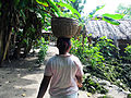 A shot from behind of an Aorigi woman carting a basket on her head. (10663173814).jpg