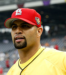 A man in a yellow shirt and a red baseball cap
