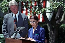 Ginsburg speaking at a lectern