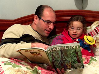 Bedtime story - A father reading his daughter a bedtime story: Madeline by Ludwig Bemelmans