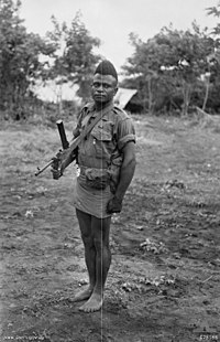 A bare-footed man with a short back and sides haircut wearing an army shirt and short skirt, carrying a weapon on a shoulder strap.