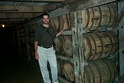 "Oak casks, shown stacked in ricks, used to store and age bourbon. Bourbon that escapes naturally from the wooden casks, as seen by the stains along the sides of the barrels, is known to distillers as the ""angel's share"""