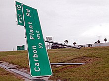 "A sign on its side, blown down by high winds, for Exit 10 that reads ""Carbon Plant Rd ½ mile"". A building and another large, green exit sign can be seen in the background."