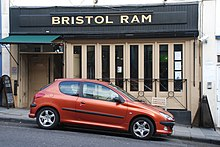 Photo of a building with slatted windows, and awning above door. An overhead sign reads Bristol Ram. A red car is parked in front on a road sloping down to the right
