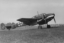A black-and-white photograph of a twin-engine fighter aircraft standing on a grass field, shown in profile.