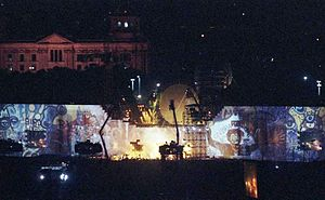 A wall covered in graffiti with a circular movie screen and lights atop it. Several cranes are visible in the center.