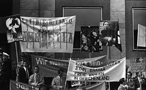 Marchers carry banners and enlarged photographs of victims at a protest in Stuttgard