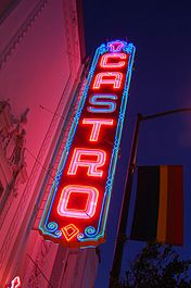 "Seen from below, a neon sign that reads ""CASTRO"" in vertical letters is lit against a night sky."