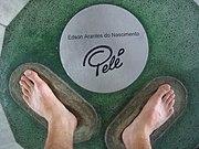 Um fã coloca seus pés na marca de Pelé na calçada da fama do Maracanã, local do gol 1000.