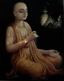 A painting of a man with shaved head and dressed in saffron robes sitting cross-legged