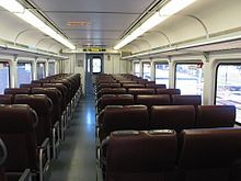 The inside of a train car during daylight, consisting of an aisle and seats on both sides of the aisle.