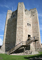 A circular castle tower with enormous jutting buttresses. There are few windows and entrance is on a upper floor, is reached by a modern staircase.