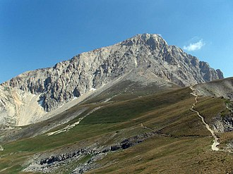 Corno Grande - Corno Grande from the south, showing the normal route contouring across the face of the mountain to the left and the more direct ascent route zigzagging towards the face