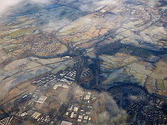 Castlecary - Castlecary from the air. The canal crosses the picture bottom left to top right (west to east). The railway is just below it with the white roof of the CMS buildings at Castlecary between them. The Red Burn (SUDS) ponds can be seen south of the Arches which are just visible. Cumbernauld's Wardpark can be seen being divided by the M80 as it heads north towards Stirling. At the bottom left the edge of Westerwood can be seen below Cumbernauld Airport. At the bottom, the small white T-shaped building is the Old Inns petrol station which separates Castlecary Road from the M80. The curve of Forest Road round Whitelees in Cumbernauld and Whitelees Roundabout which divides it from Abronhill are at the bottom right. North of Castlecary, Banknock can be seen on the left extending towards Longcroft and Dennyloanhead with Denny and Bonnybridge at the top right.