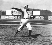 "A man in a white baseball uniform and cap throws a baseball with his right hand. The shirt of his uniform has a sock-shaped icon, which reads ""Boston"". He is looking, and throwing, to the right of the picture."