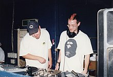 Two men stand behind a set of turntables in 1997.