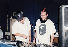 Two men stand behind a set of turntables.