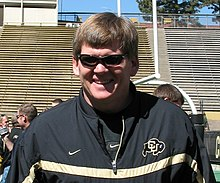 An upper body shot of a man wearing sunglasses and a black jacket with the Colorado buffalo logo (interlocked letters CU on top of a buffalo).