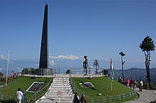 An obelisk on an elevated circular platform, with a few people standing around. Kangchenjunga is visible in the background.