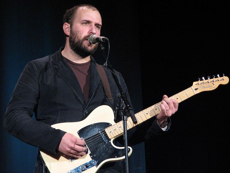 Bazan onstage with a guitar and microphone