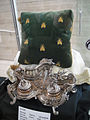 "Debbie Reynolds Auction - 015 - heavy silverplate inkwell, linen and lace tablecloth, and green bumblebee pillow from ""Desiree"".jpg"