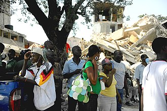 Structural violence in Haiti - Haitians walk by damaged buildings in downtown Port-au-Prince, Haiti, after the 2010 earthquake.