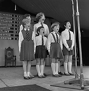 Urdd National Eisteddfod - A group of children perform at Carmarthen in 1967. The old county score board is visible behind them.