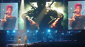 Eminem and Rihanna onstage in front of three large theater screens