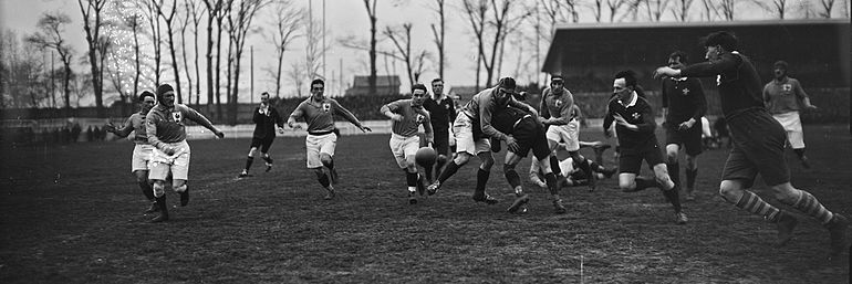 A rugby match with players from both teams bearing down on a loose ball