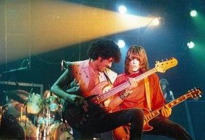 Phil Lynott plays bass guitar next to a guitarist