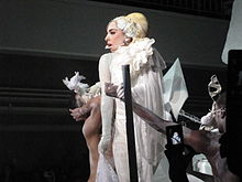 Gaga photographed from her lefft, wearing a white dress and flanked by her dancers.
