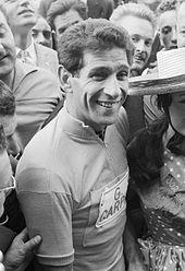 Photographie en noir et blanc d'un cycliste entouré par la foule.
