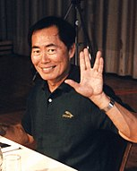 An Asian man wearing a black shirt gives a Vulcan salute.