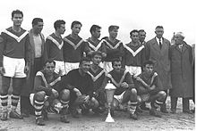 "A group of men congregate around a silver trophy on the ground in this black-and-white photograph. Five men squat beside it, while ten stand behind. The five men at the front and six of those behind wear soccer attire; ten wear dark shirts marked with a white ""V"" extending from each shoulder to meet on the chest, with white shorts and hooped socks. The eleventh player, the goalkeeper, appears to be wearing all black. The four non-players wear street clothes; one wears a t-shirt and a greatcoat, while the other three wear suits and greatcoats."