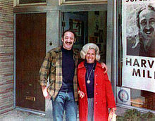 A color photograph of Milk with long hair and handlebar moustache with his arm around his sister-in-law, both smiling and standing in front of a storefront window showing a portion of a campaign poster with Milk's photo and name